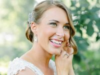 Smiling bride putting on earrings