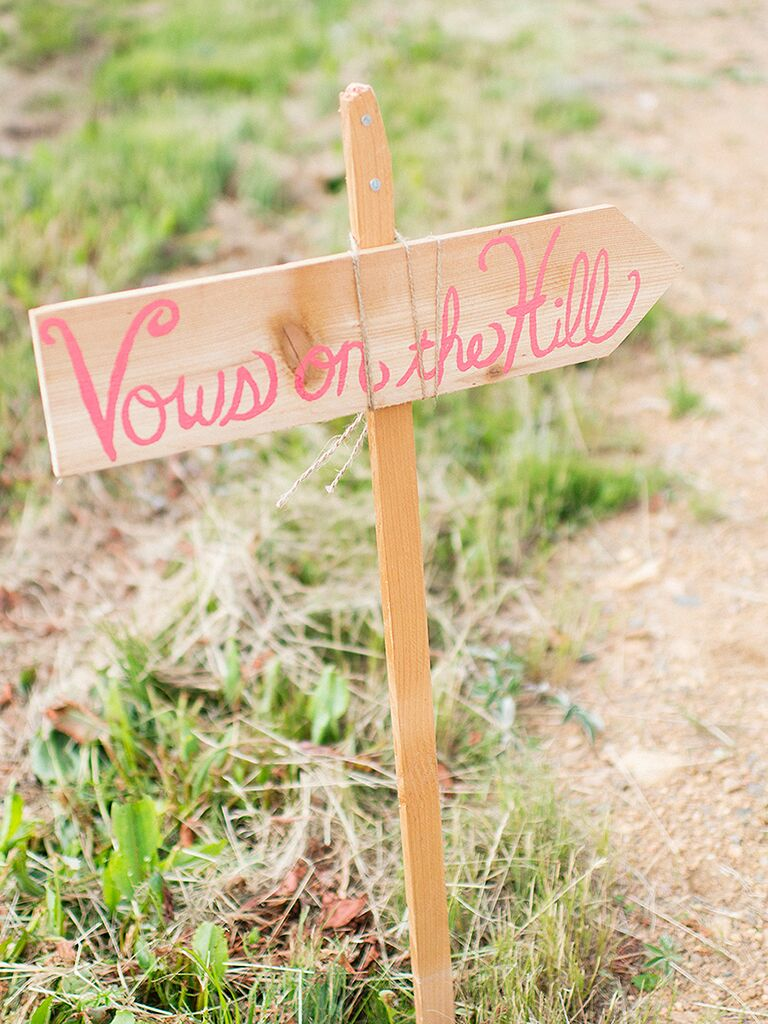 DIY wedding sign pointing to the vow location