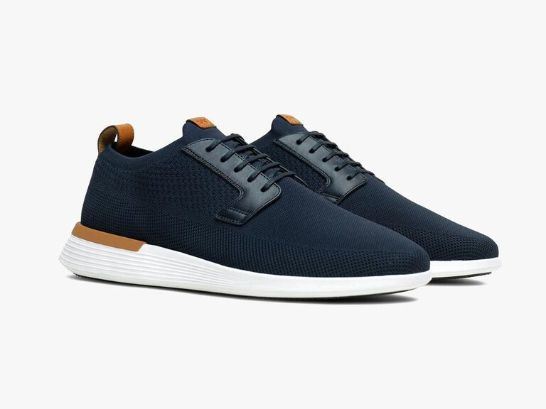 Navy sneakers with white soles and brown leather accents