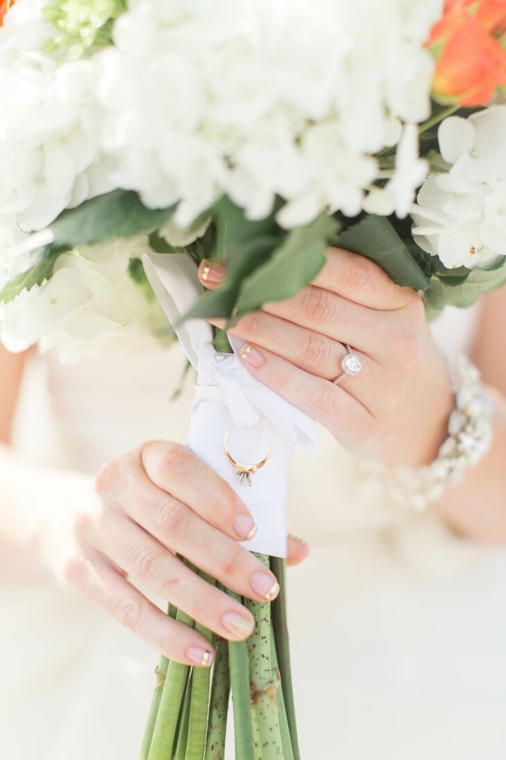 Leah's engagement ring was an oval cut diamond with a halo. An heirloom ring was attached to her bouquet wrap. Leah's nails were done with a gold French manicure.