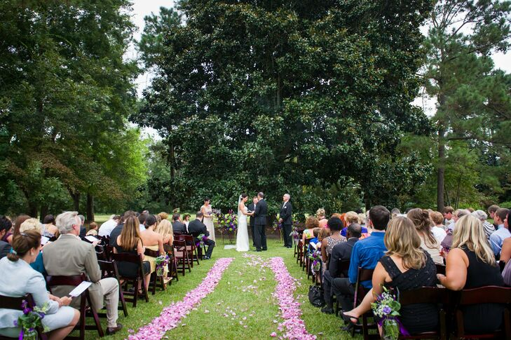 The outdoor ceremony aisle was lined with loose purple petals and wooden folding chairs.