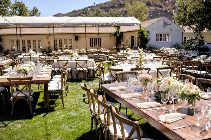The reception took place on the lawn at Triunfo Creek Vineyards in Agoura Hills, California. Wooden tables and white-cushioned chairs were arranged for guests, and the table surfaces were decorated with neutral-color flower centerpieces.