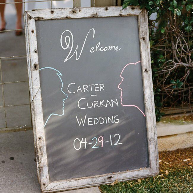 A chalkboard sign with the couple's names, silhouettes and wedding date greeted guests at the site.