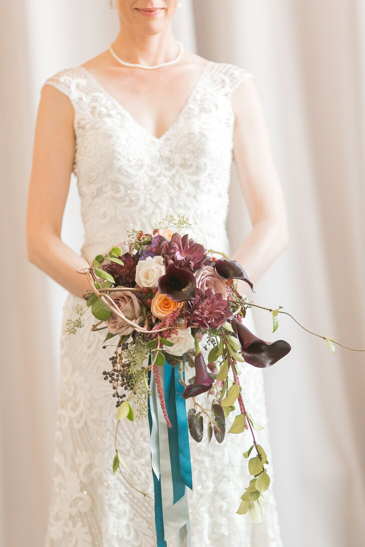 """My bouquet featured dark burgundy flowers, including calla lilies and dahlias, combined with neutral components like quicksand roses and organic elements like hypericum berries and eucalyptus, with a few cascading greens,"" she says. Her dress blended vintage inspiration with a modern, elegant design with subtle crystal beads."