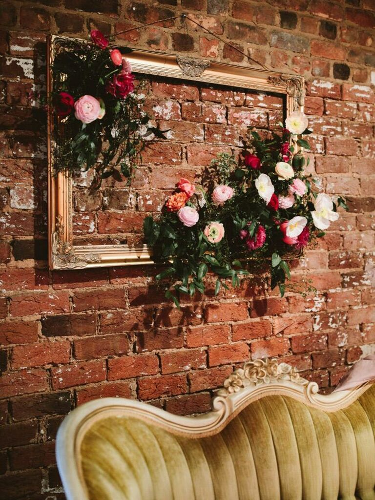 Empty vintage picture frame hanging on exposed brick wall with clusters of flowers
