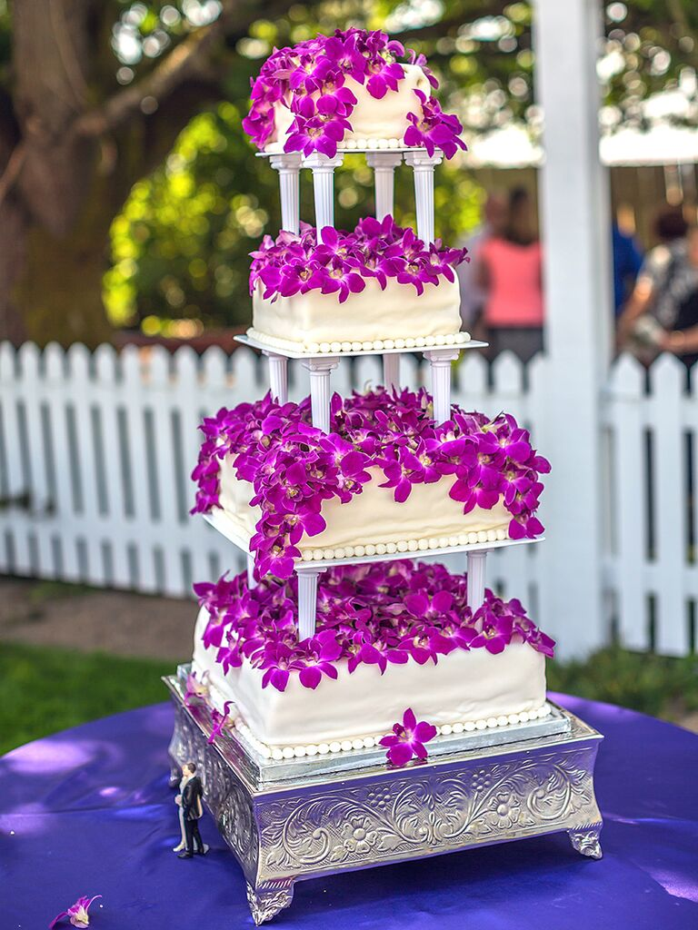 White tiered wedding cake with bright purple orchids