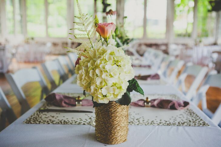 At the reception, table centerpieces were decorated with hydrangeas and garden roses arranged inside vases wrapped with twine, which were made by the bride.
