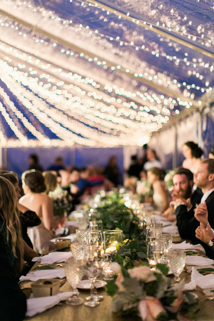 "The long reception tables were topped with a runner of vintage library card boxes filled with greenery. ""Everything looked so whimsical mixed with the twinkle lighting and the clear top tent,"" says Jenn. ""I felt like we were in a secret garden."""