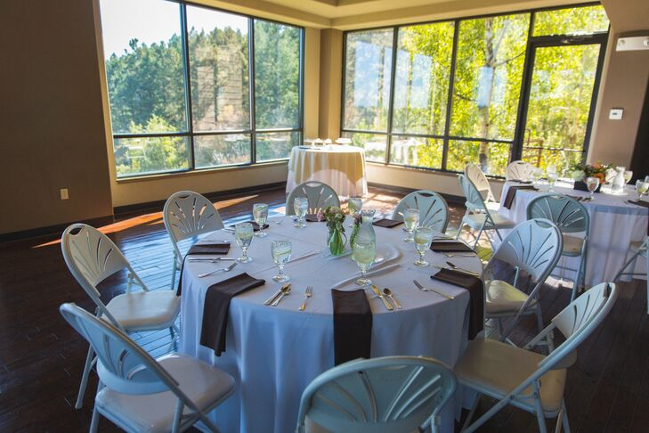 """The casual reception was inside the Pines at Genesee event building. They paired white table linens with brown napkins and small centerpieces for a simple, rustic feel. """"The lower level floor had a Colorado vibe, with its dark wood floors, large fire place and view of Denver through the large east-facing windows,"""" Abby says."""