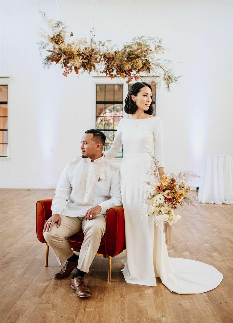 Groom in traditional Filipino wedding attire posing with bride in white wedding dress