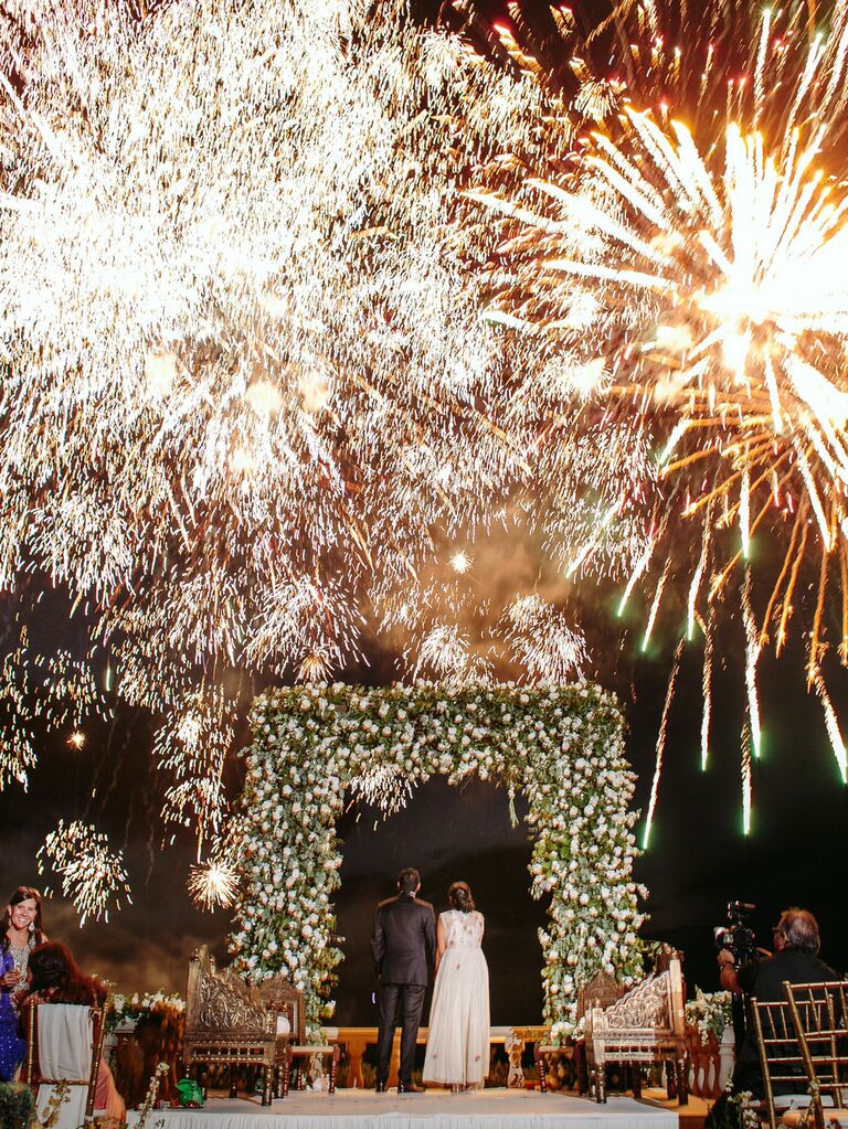 Bride and groom watching fireworks at outdoor wedding reception
