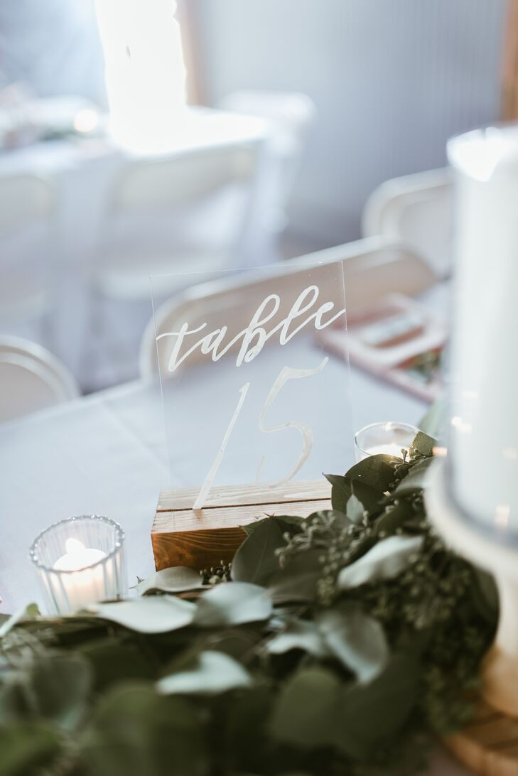 For a modern touch, table numbers were etched onto clear acrylic signs set in wooden holders.