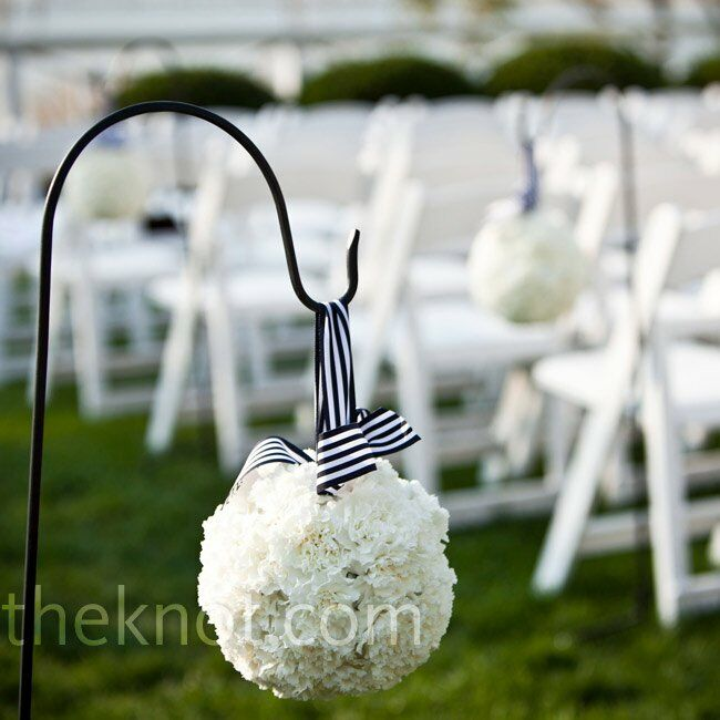 White carnation pomanders, hung on shepherd's hooks by navy and white striped ribbon, lined the aisle.