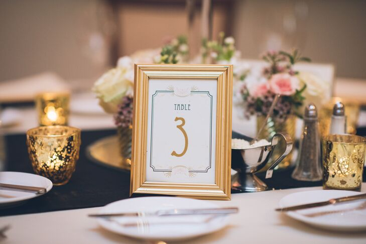 "Designed by Beacon Lane, each table captured the couple's ""Old Hollywood"" inspiration with a chic design. A geometric navy border circled encased each gold numeral. The surrounding gold frames highlighted every place setting with coordinating gold chargers and matching votive candles."