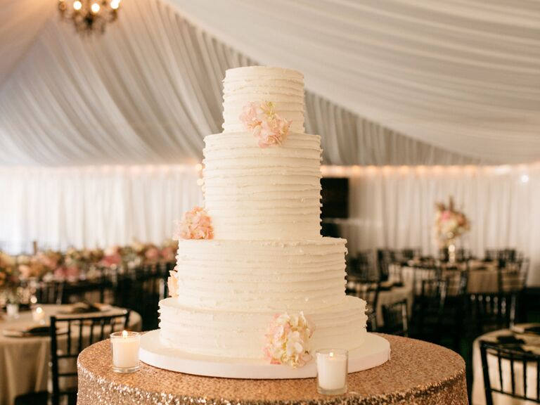 White four-tier wedding cake with blush blooms