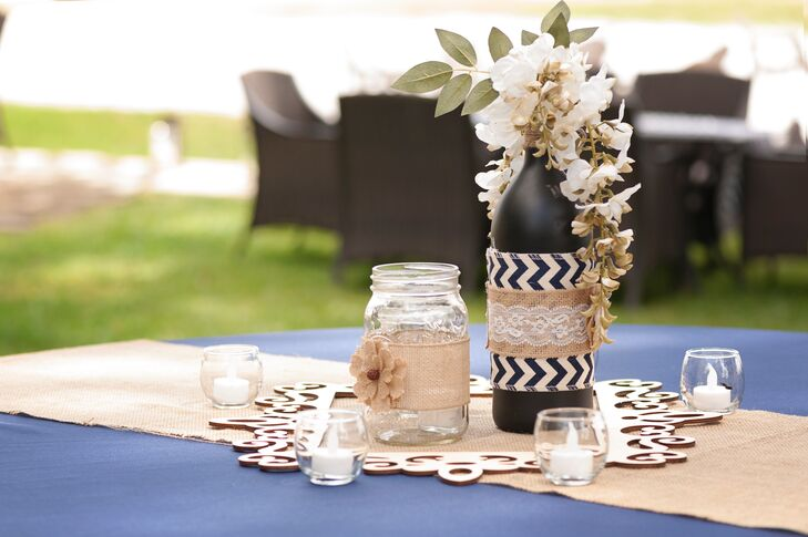 Each navy linen-covered table at the reception was met with a rustic centerpiece. Burlap, lace and chevron fabric was wrapped around each mason jar or wine bottle accent as a burlap runner accented the table. For a natural touch, Holly and Jaime also filled the bottle with a white wisteria blooms.