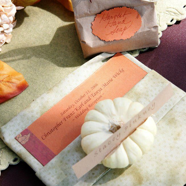 The bride's sister created handmade soaps in seasonal scents that Tatiana and Chris placed in bags at each place setting. Tatiana created the menus, escort cards, and table numbers using different patterned papers so that each card was a little different. Miniature pumpkins with guests' names affixed to them served as place cards.