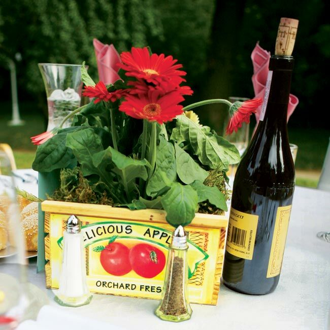 Round tables set in the apple orchard featured apple box centerpieces filled with red gerbera daisies and wooden table numbers.