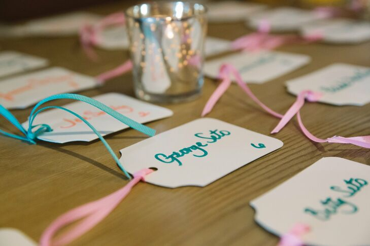 The names of each guest were handwritten on gift tags and tied with pink and teal ribbons.