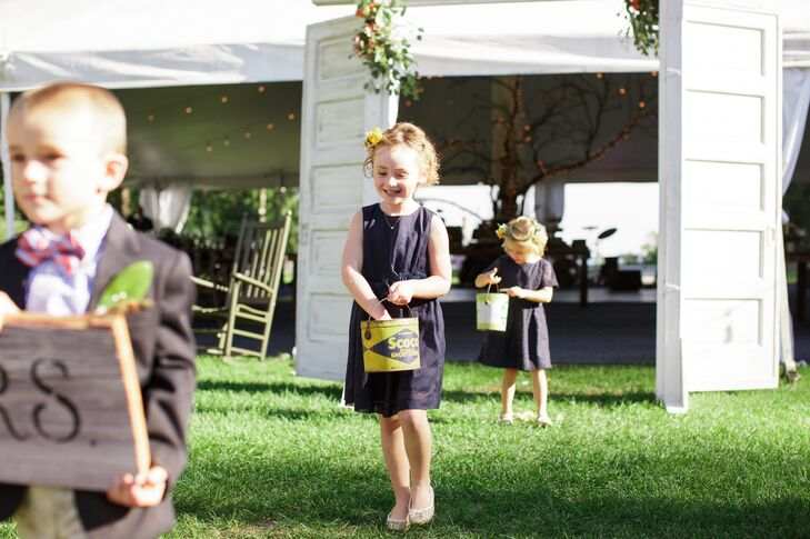 The flower girls wore navy dresses and threw rose petals from vintage pails.