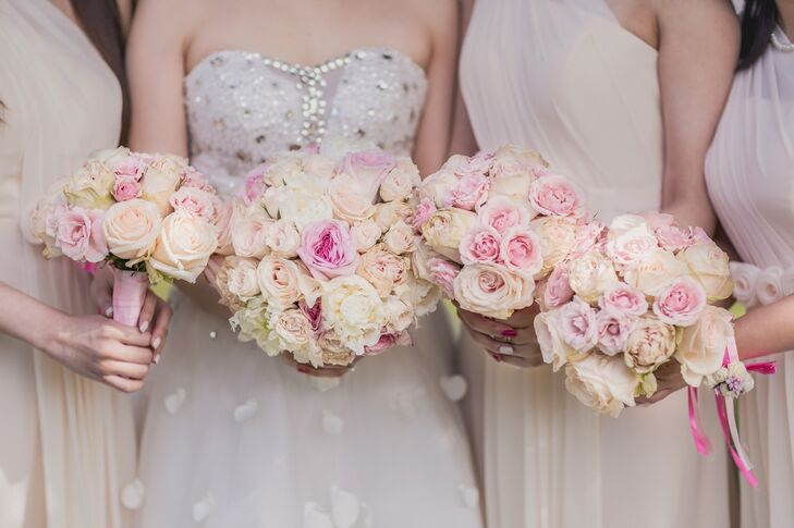 The bridesmaids carried ivory and pastel pink rose bouquets, matching Jolie's bridal bouquet.