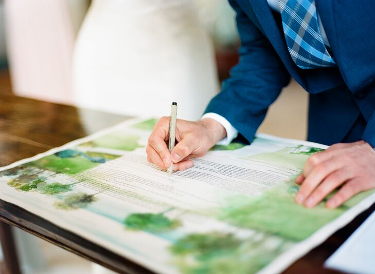 """Before the couple's Jewish ceremony, Jamie and Alex signed a ketubah (Jewish wedding contract), which was painted by the bride's father. """"He did a watercolor of the view from the balcony of the inn,"""" Jamie says. """"It felt perfect, since my dad had picked that inn for us to visit on our Maine vacation almost 10 years earlier."""""""