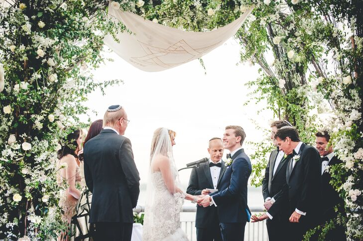 """Hayley and Jared exchanged personalized vows under an elaborate floral and vine-draped chuppah. As an extra special touch, they included a tallit handmade by Jared's late mother in her remembrance. """"Elaine made the tallit for her brother's wedding more than 20 years ago. Her brother saved it and upon learning that it had been preserved, we asked to borrow it for our ceremony,"""" says Hayley. """"We embroidered our names of he tallit, next to the other couples' names. It meant a lot to us to get married under the chuppah made by Elaine. We felt that she was there with us at the wedding ceremony."""""""