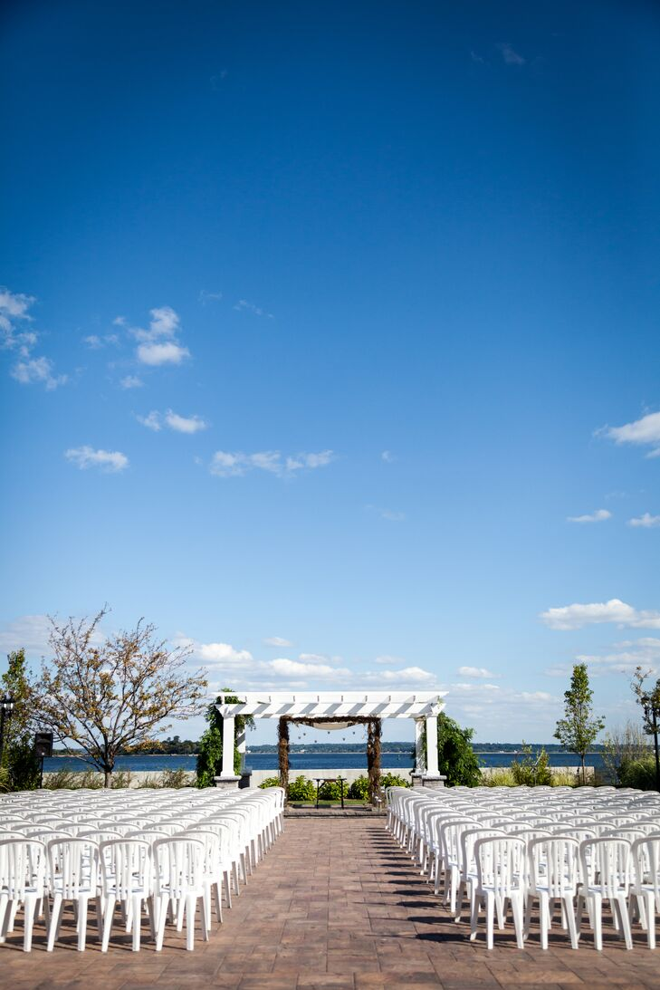 """""""The most important thing we wanted in a venue was an outdoor ceremony area,"""" Emma says. """"Greentree's beachy space overlooking the water was a no-brainer."""" Rather than filling it with decor, they highlighted the venue with a natural chuppah and rows of white chairs."""