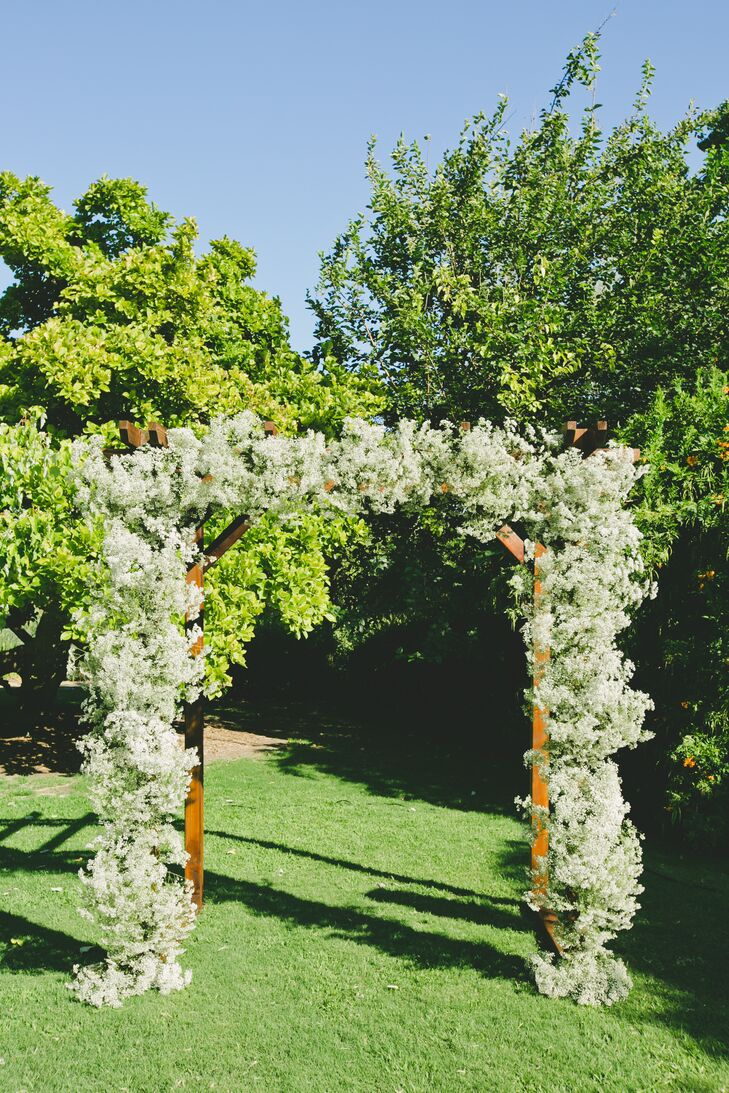 The white blossom-covered arbor that Esme and Matthew stood under during the ceremony at the Los Angeles County Arboretum and Botanic Garden in Arcadia, California, was designed and built by the groom and his brothers.