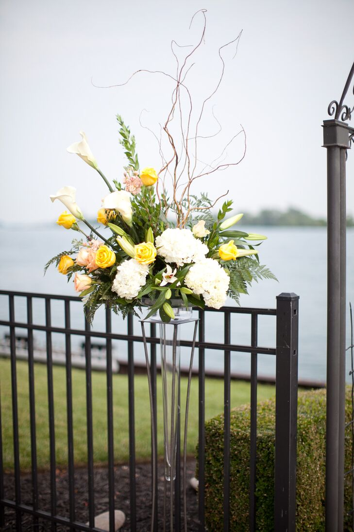They picked up on the natural hues of the Detroit, Michigan, waterfront, and decorated the metal arbor with twin arrangements. Yellow and peach roses, white calla lilies, white orchids, greenery, curly willow, pink delphiniums and white hydrangeas topped these modern clear stands on both sides of the accent.