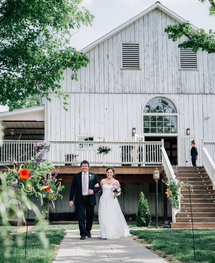 The ceremony took place outdoors by the Barn at Boones Dam in Bloomsburg, Pennsylvania. The aisle was lined with shepherd's hooks with hanging wildflowers.
