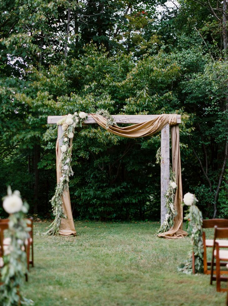 """Christine and Adam let the landscape take center stage for the ceremony, incorporating elements that played up the setting's woodland vibe. The aisles were lined with lush garlands of eucalyptus and a wooden arch draped in copper cloth, and an eye-catching arrangement of greenery and ivory florals framed the couple as they said their """"I dos."""" The pair customized the ceremony with readings from Rumi, Thoreau and Pablo Neruda, as well as instrumentals of their favorite tunes. """"We wanted our ceremony to speak more to our journey together and the roles that our friends and family played in it,"""" Christine says. """"Addison and I met almost exactly 10 years before the wedding—freshman year at UVM—so our wedding felt like this climactic moment that everyone present was a part of, and we were excited to honor that during the ceremony."""""""