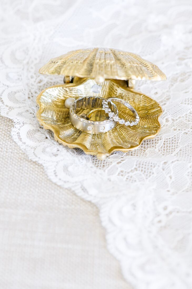 """Nicole and Bren left no detail overlooked when it came to infusing their waterfront celebration with beachy flair. The pair housed their wedding rings in a glistening gold seashell ring box before they said """"I do"""" along the shore."""