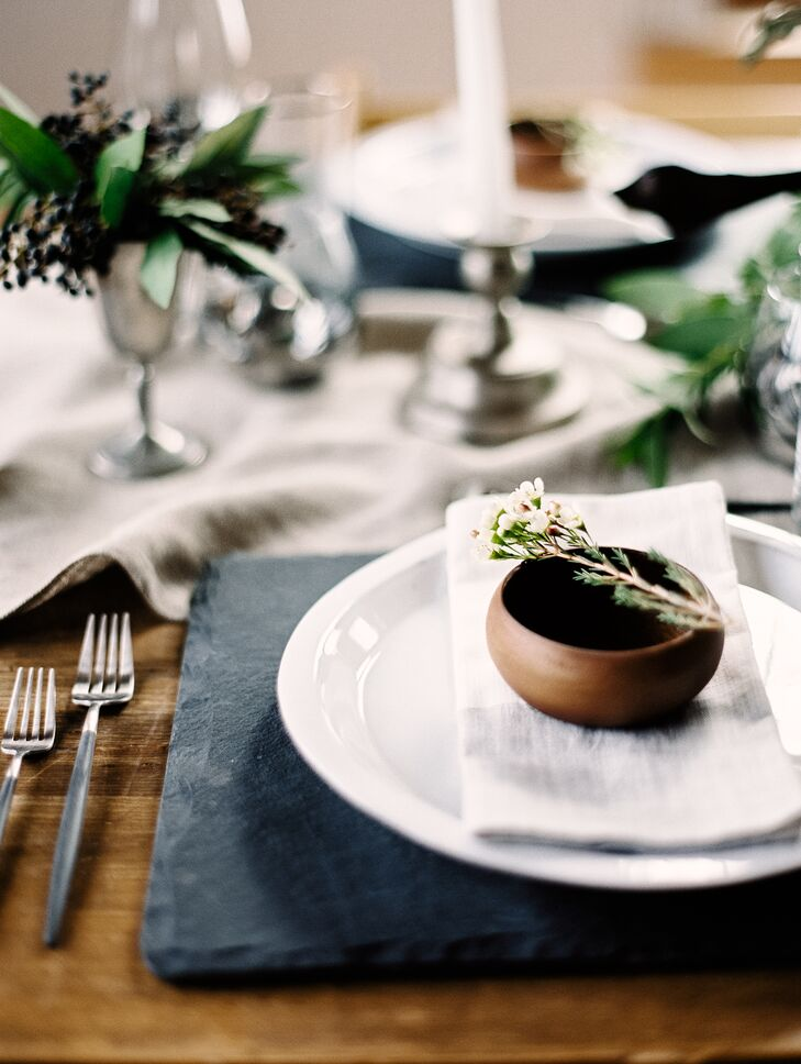 Slate place mats set a rustic but elegant tone for the settings. Small wooden bowls decked with tiny white flowers and herbs brought a touch of warmth to the masculine array.
