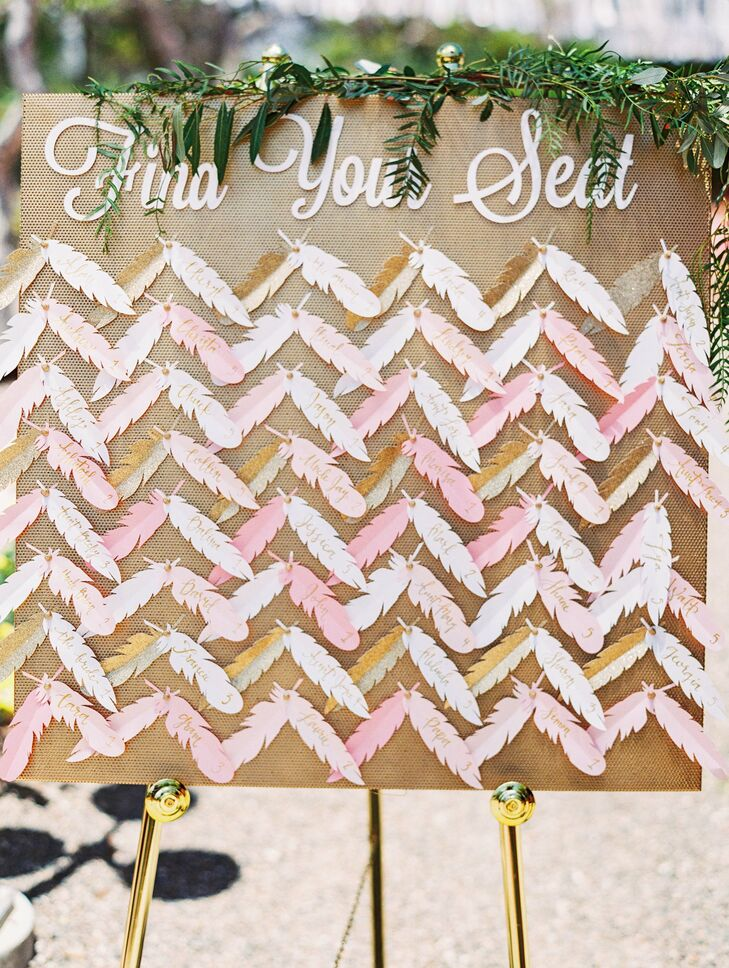 Feather-shaped escort cards in different shades of pink hung on a brown board, which had accents of green garland at the top. The playfully designed cards reflected the wedding's glamour-packed style.