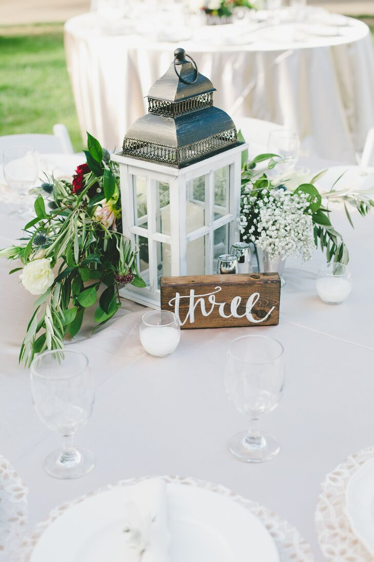 White lanterns were placed at the center of each reception table. A semicircle arrangement of deep red and white florals, greens and herbs surrounded each lantern. Small votive candles tied the arrangement together. Wooden blocks with hand-painted calligraphy served as table numbers.