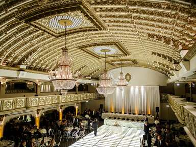 Gilded wedding reception venue with chandeliers