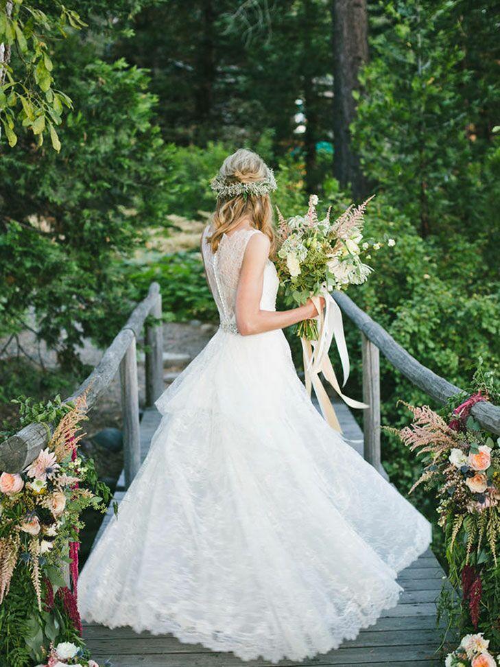 Bride spinning in wedding dress on a bridge