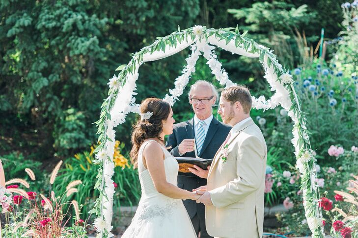 The couple exchanged their vows outdoors in front of a white floral arch.