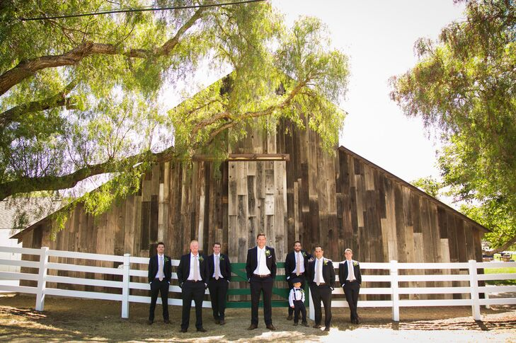The gentlemen wore navy blue suits with white shirts and blush ties to coordinate with the bridesmaid dresses. They paired them with brown leather shoes and belts. The ring bearer wore a similar ensemble with a white shirt and navy suspenders, bow tie and pants.