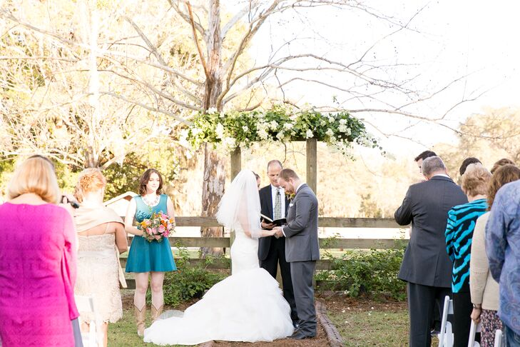 "Katie and Austin's ceremony beautifully highlighted the natural scenery at Isola Farms in Groveland, Florida. ""It already had a darling little gate and archway that created the perfect altar,"" Katie says. They let the arch serve as their main decor with a garland of eucalyptus, greenery and white hydrangeas that overflowed from the top. The service also had an extra dose of personalization since Katie's father walked her down the aisle and then married them. (How sweet is that?)"