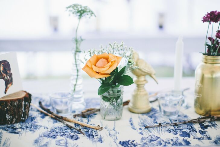 Rachel and Brent combined vases and mason jars with flowers and ceramic birds to create laid-back centerpieces. Blue and white toile runners tied the look together.