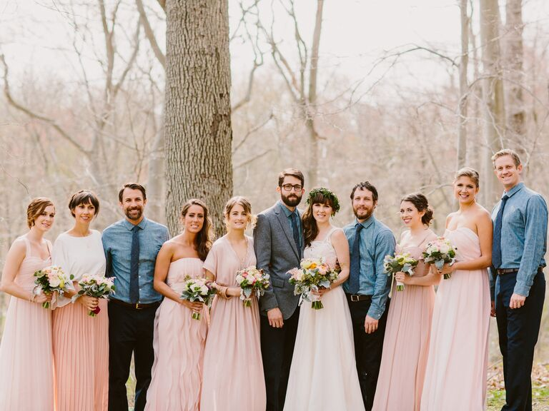 Uneven number of groomsmen and bridesmaids. Attendants are wearing blush floor-length dresses and chambray shirts with ties.