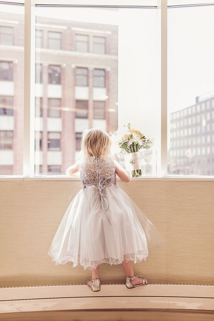 One of the couple's two flower girls held Amber's bouquet of white chrysanthemums and blush roses while gazing at downtown Kalamazoo before the ceremony.