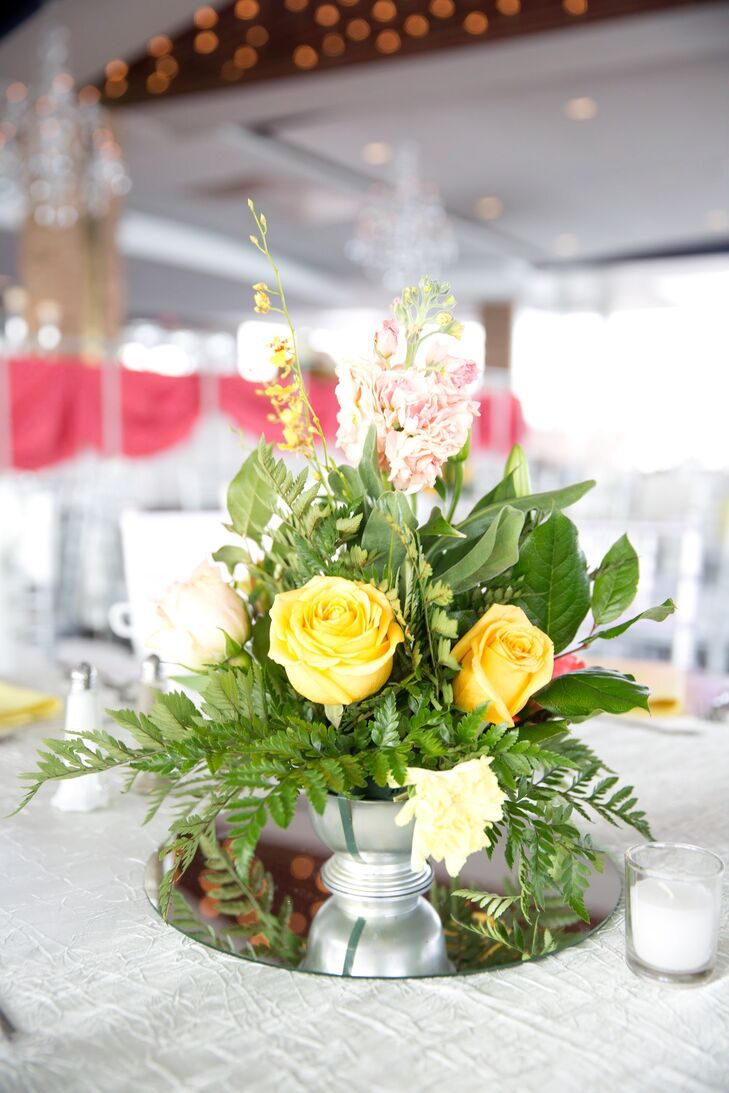 Ebony and Jeremy wanted a little variety, so they chose two centerpiece styles. For the low arrangements, yellow and peach roses, pink delphiniums and tons of greenery were placed in these silver pedestal vases. A circular mirror accent was also set below them.