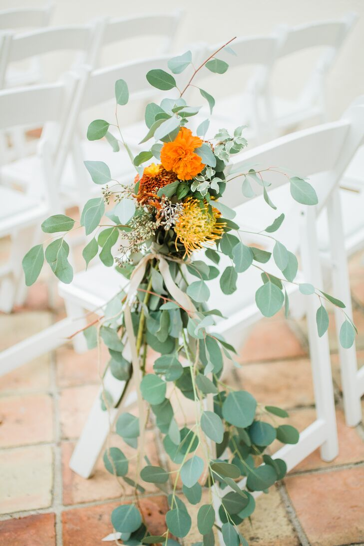 Pew markers of wild greens and orange florals tied with champagne ribbon marked the courtyard ceremony aisle. The flowers included vibrant orange dahlias, carnations and pincushion proteas with seeded eucalyptus.