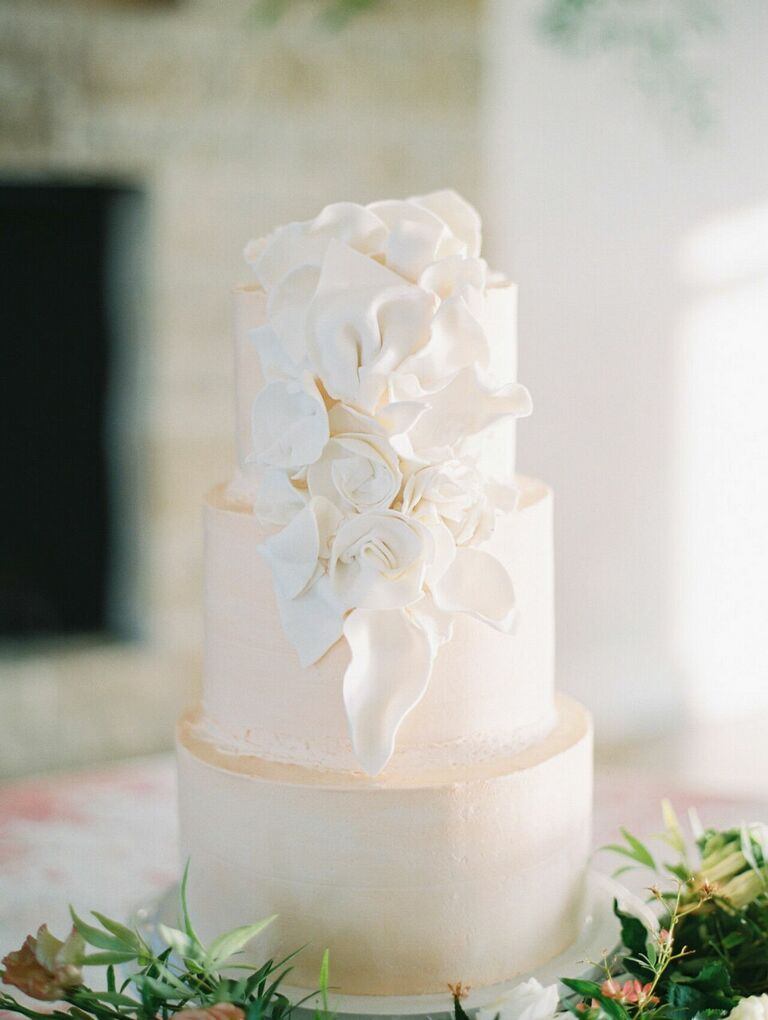 Three-tier white wedding cake with white floral decoration