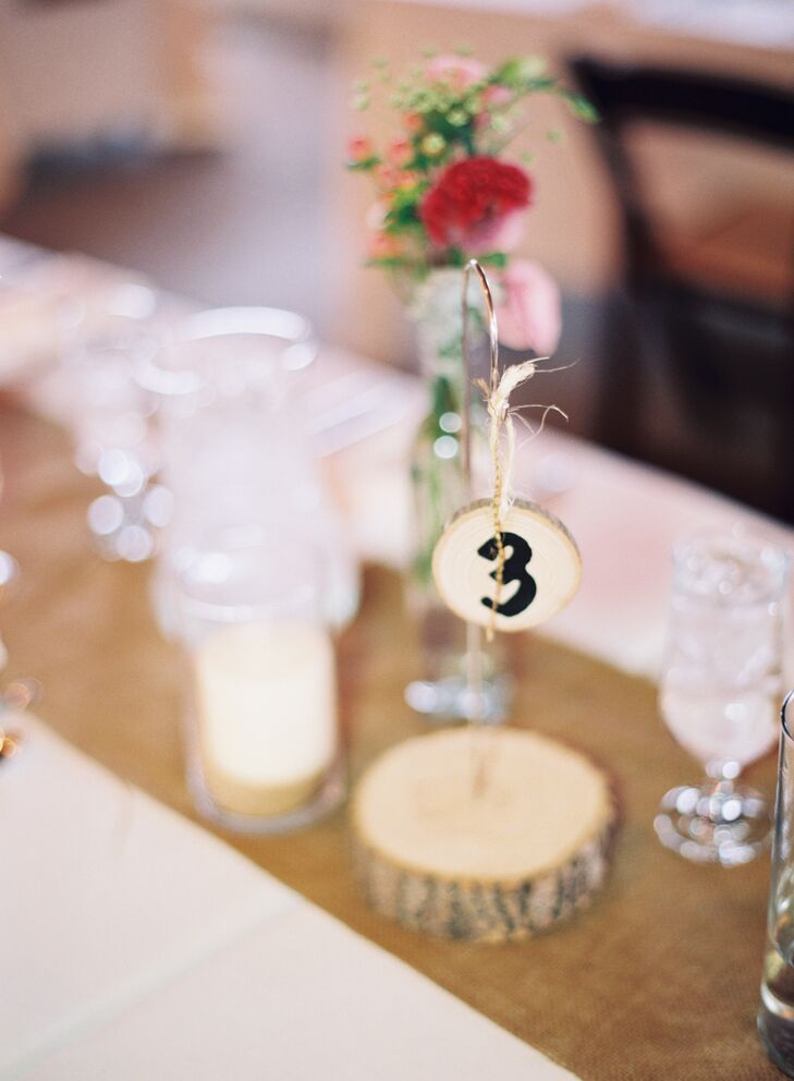 Table numbers were hung from small shepherd's hooks that stood on wood slabs.
