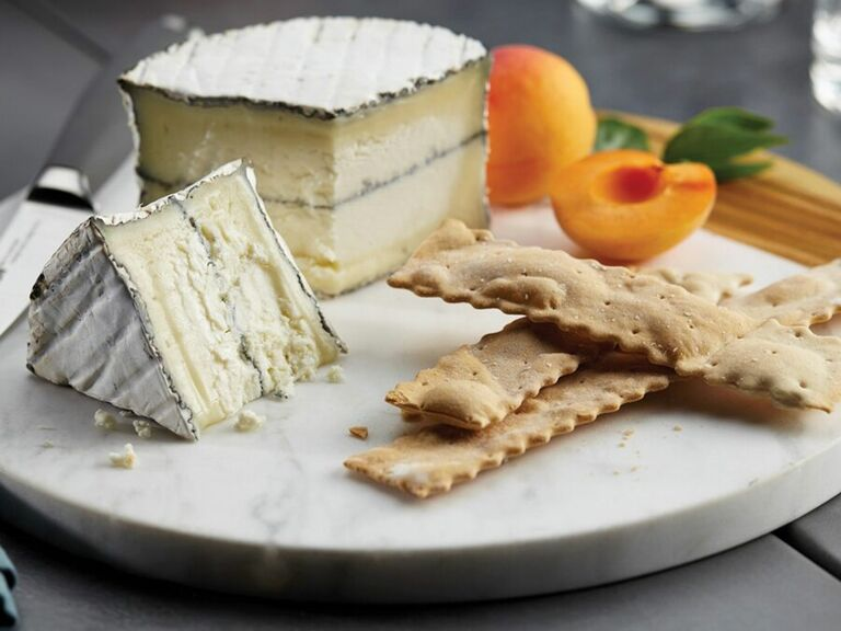 cheese and crackers on marble and wood serving board