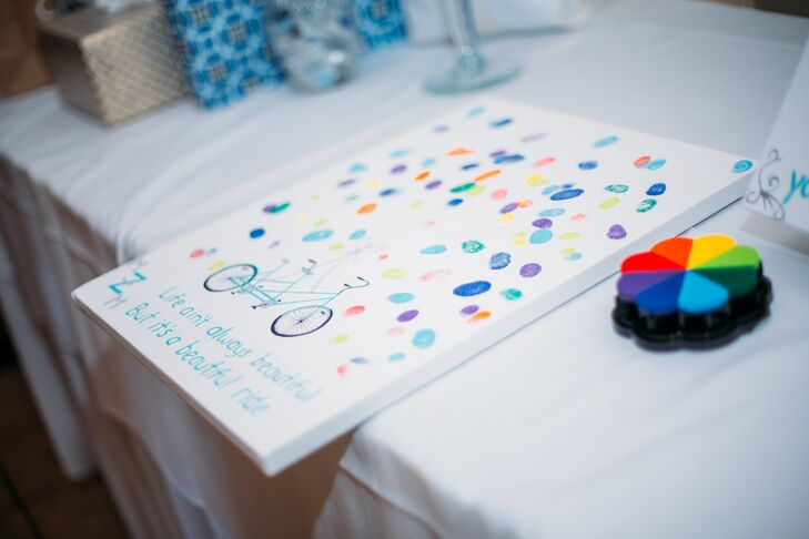 Guests left colorful fingerprints on the couple's fingerprint guest book, which had an illustration of a tandem bicycle at the bottom, a nod to Matt's love of biking.